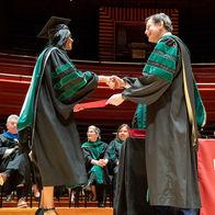 Larry Kaiser shaking a graduates hand